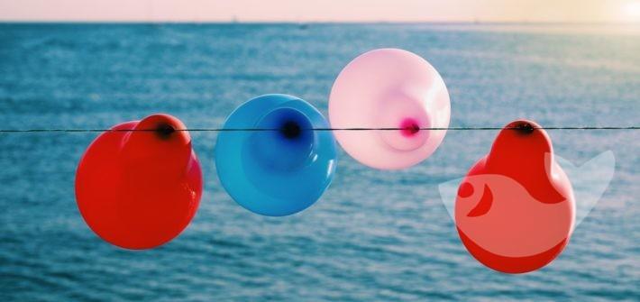 Luftballons an Leine vor Ozean